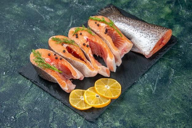 Vista laterale dei pesci crudi freschi verdi pepe e fette di limone sul vassoio di colore scuro sulla tabella dei colori della miscela nera blu