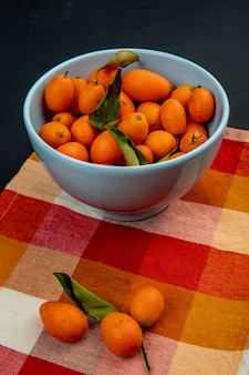 Side view of fresh ripe kumquat fruits in a blue bowl on plaid napkin on black surface