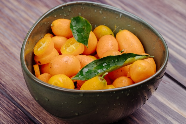 Side view of fresh ripe kumquats with water drops in a bowl on rustic wood