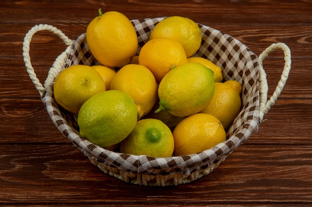 Side view of fresh ripe lemons in a white wicker basket on wood