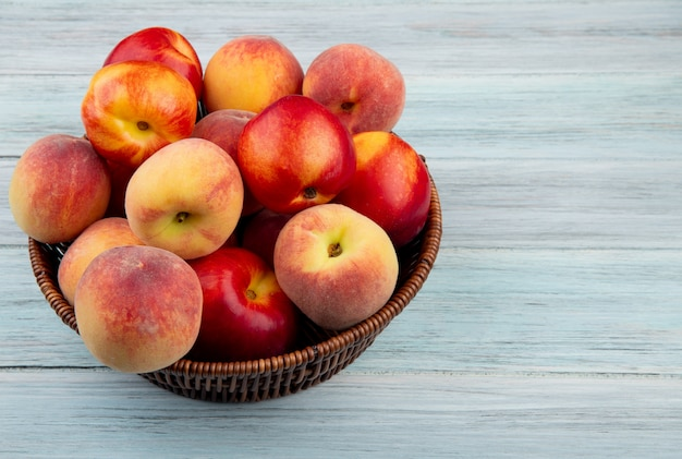 Side view of fresh ripe nectarines and peaches in a wicker basket on  rustic wooden background