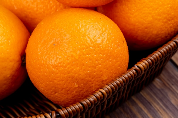 Side view of fresh ripe oranges in a wicker basket on wooden surface