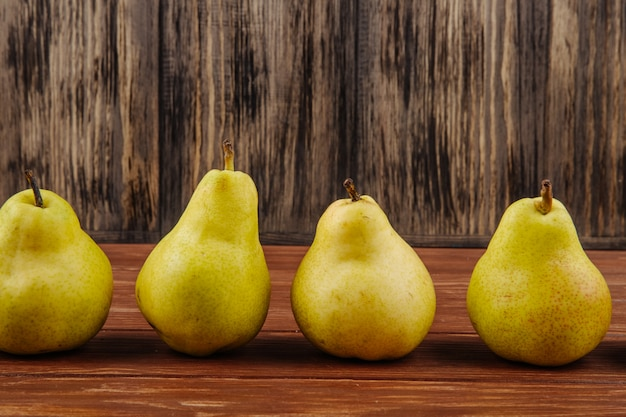 Side view of fresh ripe pears in a line on a wooden background