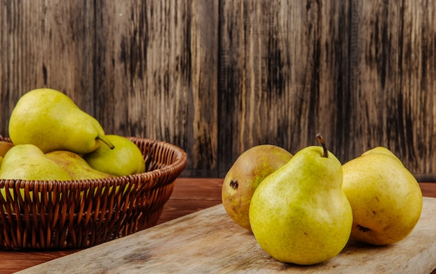 Side view of fresh ripe pears in a wicker basket and on a cutting board on a wooden background