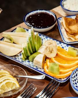 Side view of fresh sliced fruits bananas apples kiwi and orange on platter