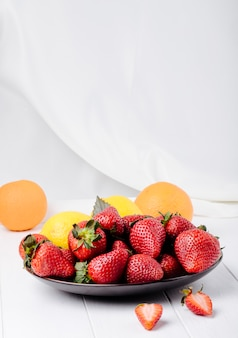 Side view fresh strawberry with lemon basil and orange on white background