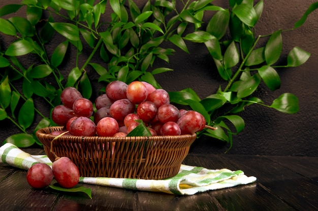 Side view of fresh sweet grape in a wicker basket on wooden surface on green leaves table