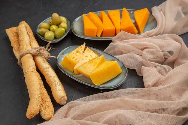 Vista laterale di fette di formaggio fresco e gustoso su un asciugamano e olive verdi su sfondo nero