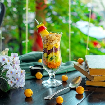 Side view of fresh vegetable salad carrot cucumbers pineapple corns in a glass on wooden table