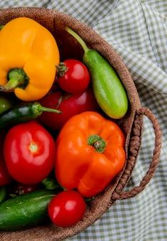 Vista laterale di verdure fresche pomodori maturi peperoni colorati peperoncini verdi e cetrioli in un cesto di vimini sul tessuto plaid