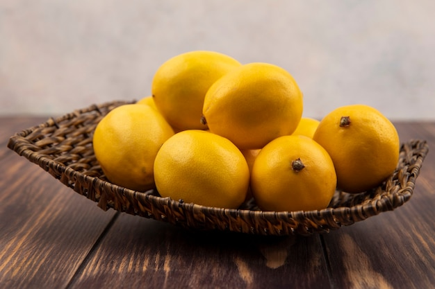 Vista laterale di limoni gialli freschi su un vassoio di vimini su una superficie di legno