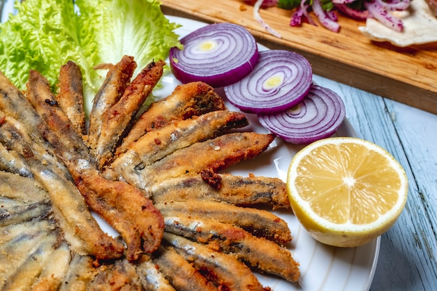 Side view fried anchovy with red onion lettuce and slice of lemon on a plate