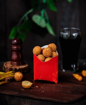 Side view of fried breaded cheese ball in cardboard bag on wooden table