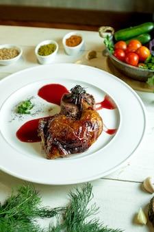 サイドビュー野菜とスパイスのバスケットが付いている皿にソースとフライドチキンの脚