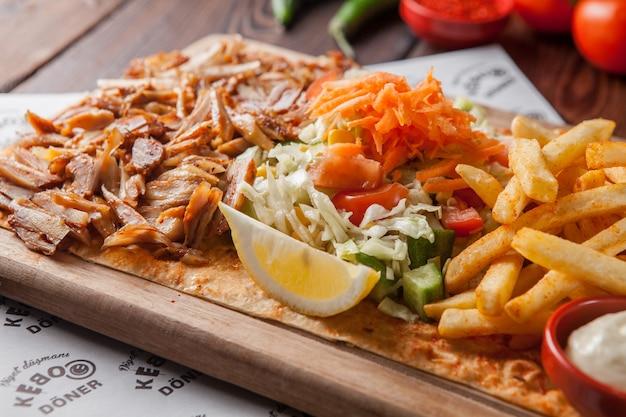 Pezzi del pollo fritto di vista laterale con il limone e patate fritte ed insalata in piatto di legno