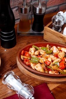 Vista laterale del pollo fritto e delle verdure su una tavola di legno