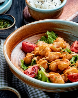 Side view of fried chicken with tomatoes and sauce on lettuce on a plate on rustic