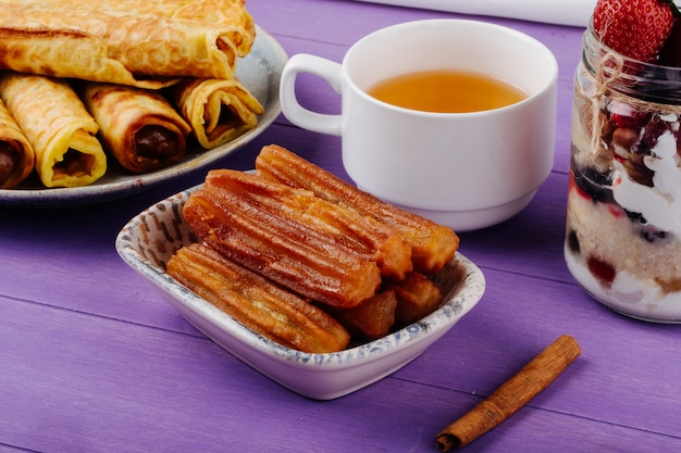 La vista laterale della pasta fritta della pasta con miele è servito con una tazza di tè verde e bastoncini di cannella sulla tavola di legno porpora