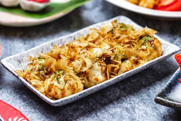 Вид сбоку жареные пельмени с соусом из сушеной кожи лосося и приправы на тарелке