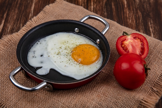 Жареное яйцо на сковороде с помидорами на бежевой салфетке на деревянном фоне, вид сбоку
