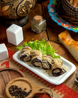 Side view of fried eggplant rolls with walnuts and mayonnaise on a plate on a wooden table