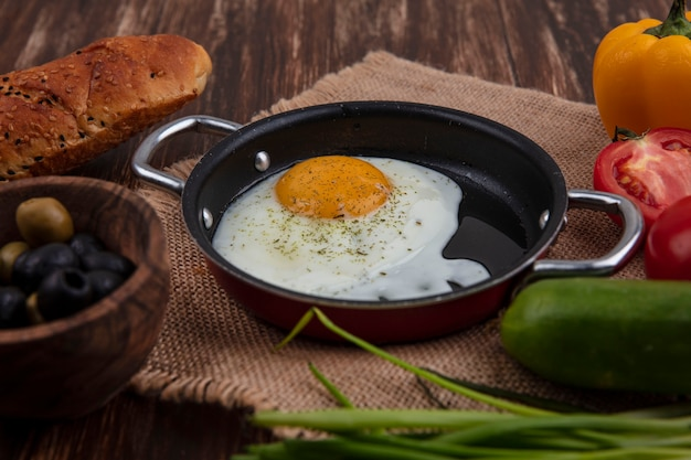 Side view fried eggs in a frying pan with green onions  olives  tomatoes  cucumbers and a loaf of bread on a wooden background