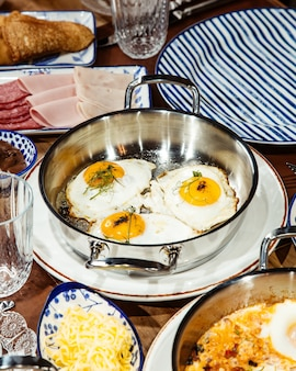 Side view of fried eggs in a pan on wooden table