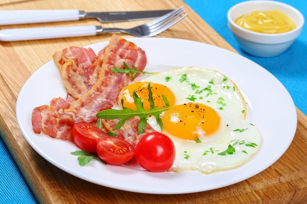 Side view of fried eggs with bacon and tomatoes