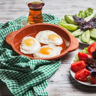 Вид сбоку жареных яиц с нарезанными помидорами и нарезанными огурцами и стаканом чая в глиняной тарелке