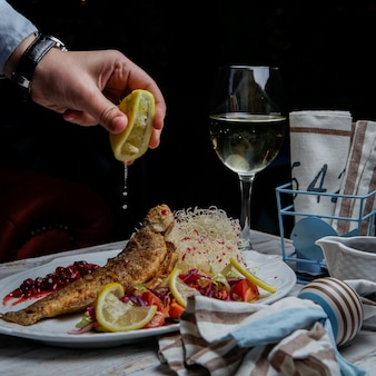 Side view fried fish with glass of wine and lemon and human hand in white plate