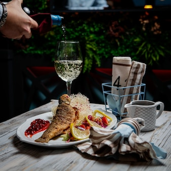 Side view fried fish with glass of wine and wine bottle and human hand in white plate