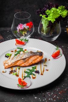 Вид сбоку жареной рыбы с помидорами и рукколой