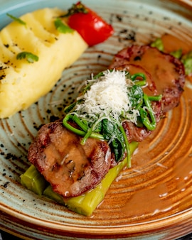 Вид сбоку жареного мяса на спаржу с картофельным пюре и зеленью в тарелке