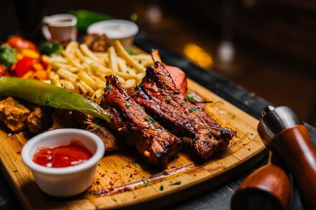 Вид сбоку жареного мяса с картофелем фри и кетчупом