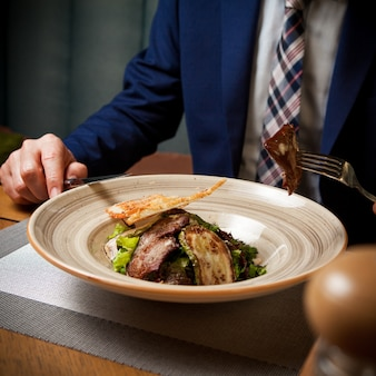 Вид сбоку жареного мяса с жареными цуккини и крекерами и человеческой рукой и вилкой в круглой тарелке