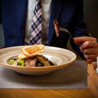 Вид сбоку жареного мяса с жареными цуккини и крекерами и человеческой рукой в круглой тарелке