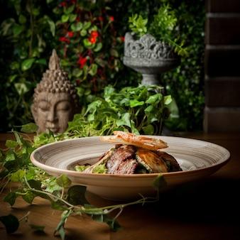 Вид сбоку жареного мяса с жареными цуккини и виноградной ветвью и головой статуи в круглой тарелке