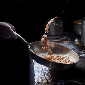 Вид сбоку жареный фарш с кастрюлей и человеческой рукой в печи