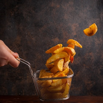 Side view fried potatoes with human hand in grid for deep frying