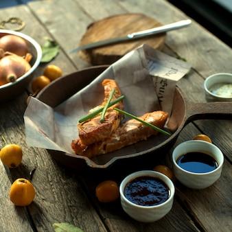 Vista laterale fritto pesce rosso in una padella sul giornale con cipolle e salse