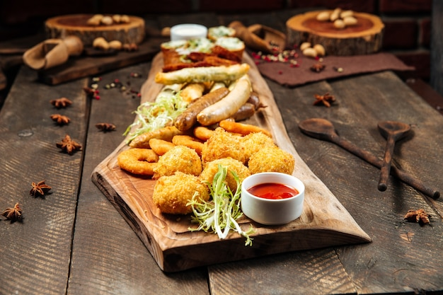 Side view on fried salty beer snacks on the wooden board with sauces