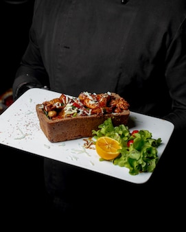 Vista laterale di calamari fritti e polpo con formaggio e patate ia un pane sostenuto