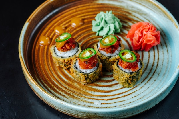 Вид сбоку жареные суши роллы с васаби и имбирем на тарелке