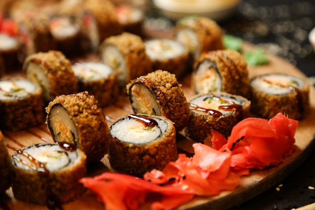 Side view fried sushi rolls with wasabi and ginger on a stand