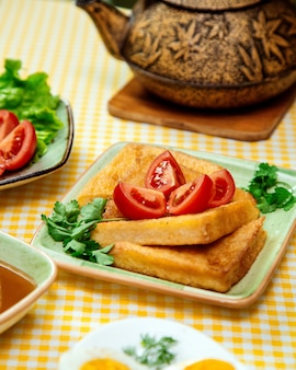 Side view of fried toasts with fresh tomatoes and parsley on plate