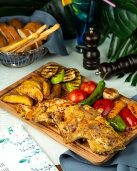 Side view fried tobacco chicken with potatoes and grilled vegetables on a wooden board