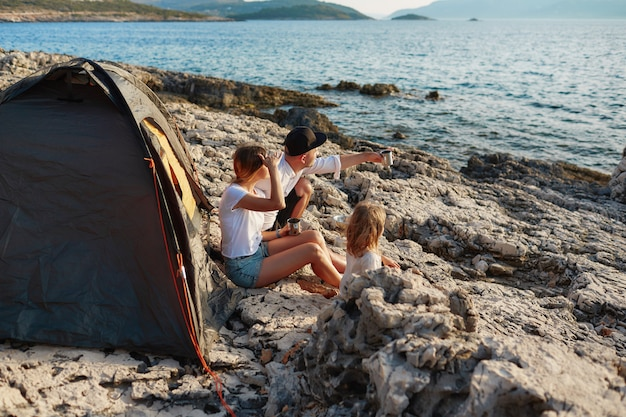 Side view of friendly family sitting near tent at rock beach, admiring sea.