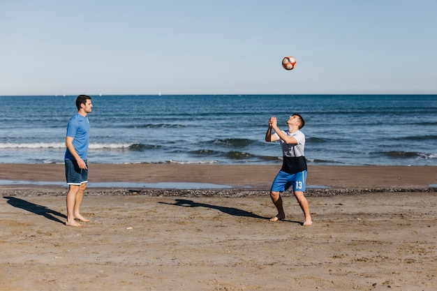 Side view of friends playing football at the beach