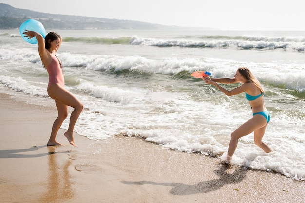 Вид сбоку друзей, играющих на пляже