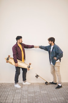 Side view of friends with skateboards
